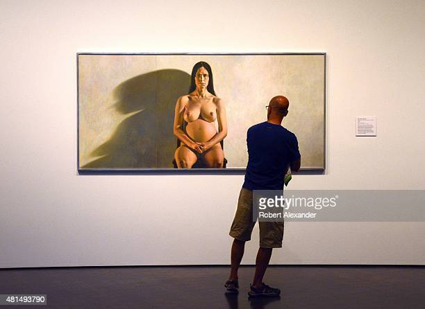 A visitor at the Denver Art Museum in Denver Colorado admires a 1973 painting of a nude pregnant woman by Colorado artist Chuck Forsman titled...