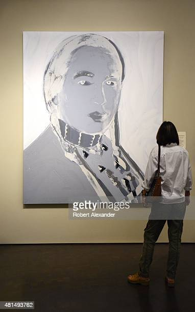 A visitor at the Denver Art Museum in Denver Colorado admires a polymer paint and silkscreen painting by Andy Warhol titled 'The American Indian '...