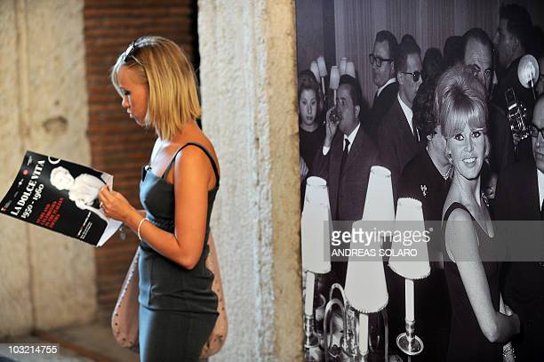 A visitor at the premier of the exhibition of photographs of the 1960 film by Frederico Fellini La dolce vita stands by a photograph by Brigitte...