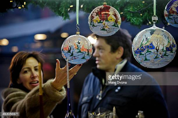 A visitor browses christmas decorations at the Christmas market at the Old Town Square on December 2 2013 in Prague Czech Republic Christmas markets...