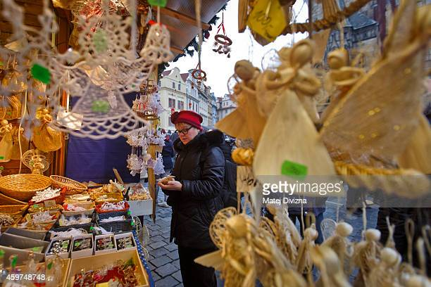 A visitor browses christmas decorations at the Christmas market at the Old Town Square on November 30 2014 in Prague Czech Republic Christmas markets...