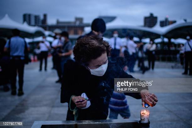 Visitor burns incense to pay tribute to the atomic bomb victims in front of the cenotaph at the Hiroshima Peace Memorial Park in Hiroshima on August...