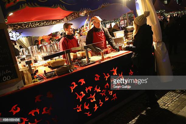 A visitor buys raclette cheese at a stall at the annual Christmas market at Gendarmenmarkt on its opening day on November 23 2015 in Berlin Germany...