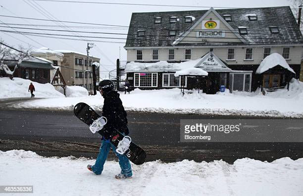 A visitor carrying a snowboard walks on a road in the Hirafu area of Kutchan Hokkaido Japan on Saturday Feb 14 2015 Japan had a record number of...