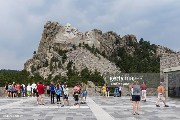 CONTENT] Visitor Center view showing the Mount Rushmore memorial with tourists looking at the memorial and taking pictures An American icon in the...