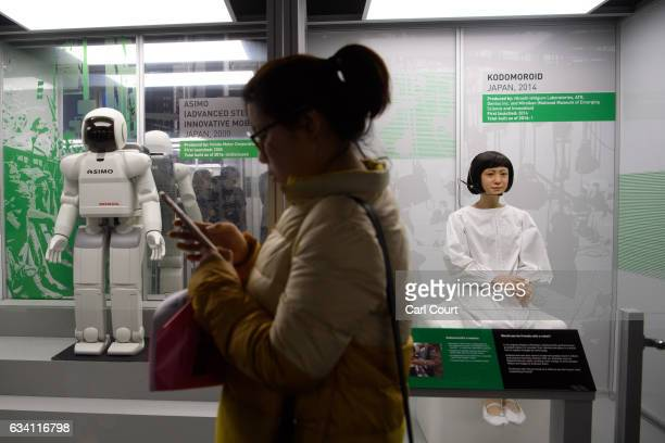 Visitor checks her phone as she walks past a Kodomoroid communications android and ASIMO robot during the press preview for the 'Robots' exhibition...