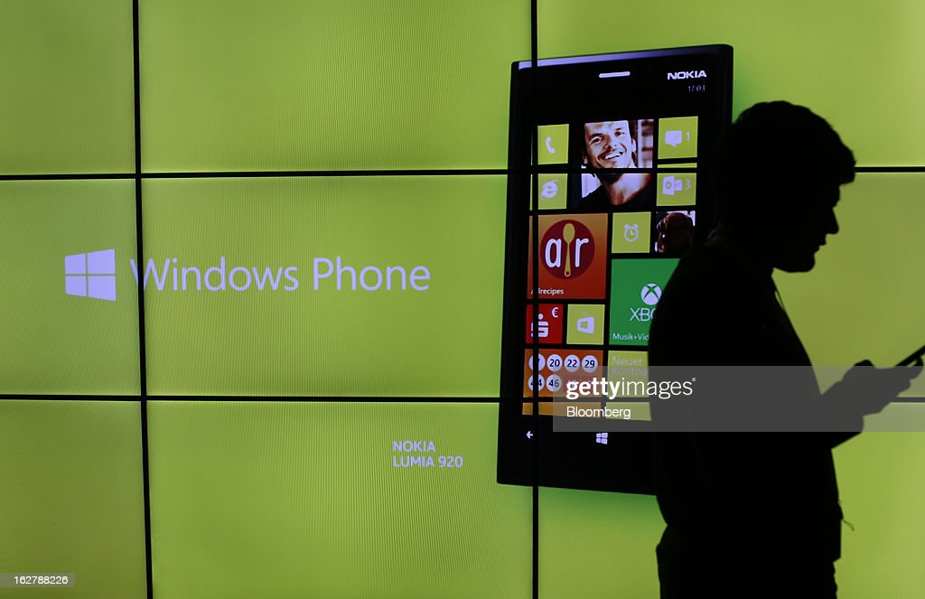 A visitor checks his mobile device in front of a video advertisement for a Nokia Lumia 920 Windows Phone at a media event at the Hotel Rey San Carlos during the Mobile World Congress in Barcelona, Spain, on Tuesday, Feb. 26, 2013. The Mobile World Congress, where 1,500 exhibitors converge to discuss the future of wireless communication, is a global showcase for the mobile technology industry and runs from Feb. 25 through Feb. 28. Photographer: Simon Dawson/Bloomberg via Getty Images
