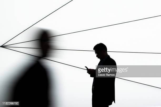A visitor checks his mobile phone on day 2 of the GSMA Mobile World Congress 2019 on February 26 2019 in Barcelona Spain The annual Mobile World...