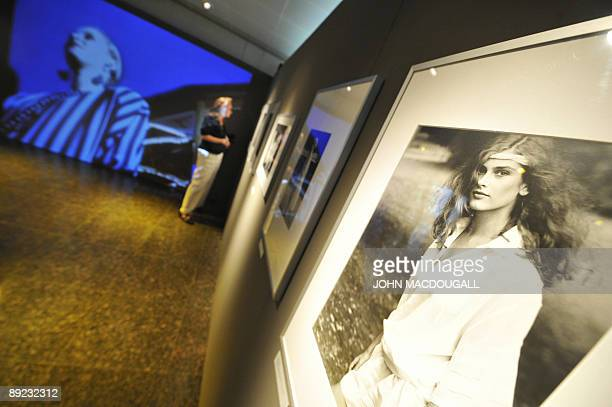 A visitor checks out photographs on display at the exhibition In Grenzen Frei Mode Photography Underground in Berlin July 14 2009 The exhibition...