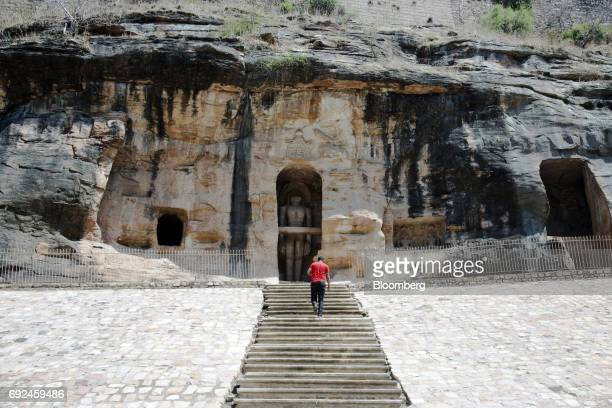 A visitor climbs up a flight of steps towards caves containing Jain religious idols carved from rock at Gopachal hill in Gwalior Madhya Pradesh India...
