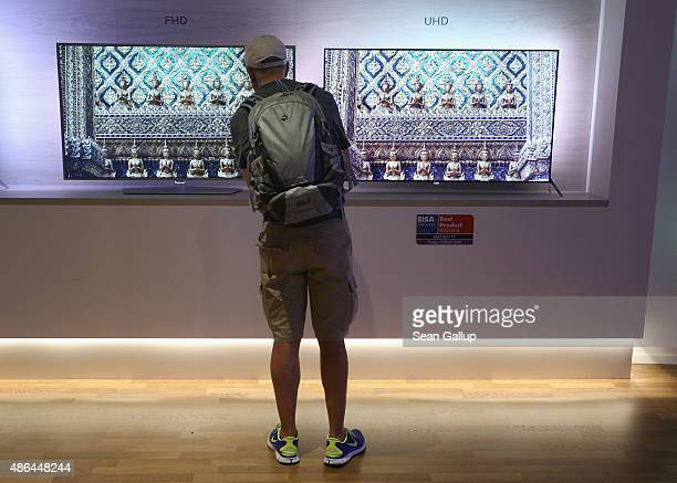 A visitor compares FullHD and UHD televisions at the Philips stand at the 2015 IFA consumer electronics and appliances trade fair on September 4 2015...