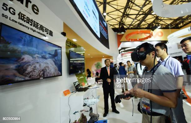 A visitor controls the unmanned submersible with virtual reality headset adopting 5G technology during Mobile World Conference 2017 on June 28 2017...