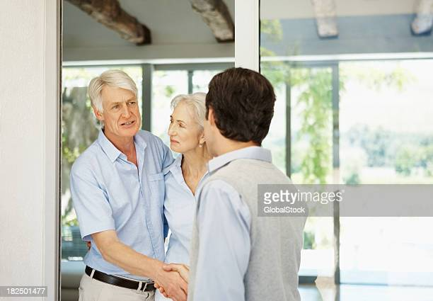 Visitor - Couple greeting a man at their door