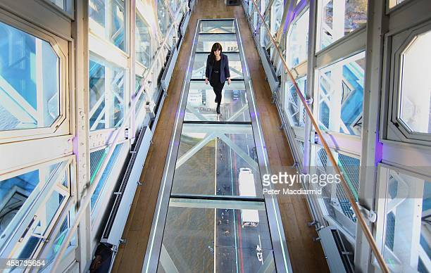 A visitor crosses Tower Bridge's new glass walkway on November 10 2014 in London England Unveiled today the glass floor panels along the bridge's...