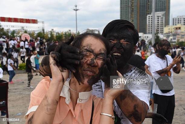 A visitor daubs rice ash on another's face during the Face Painting Festival in Puzhehei Resort of Qiubei County on July 18 2016 in Wenshan...