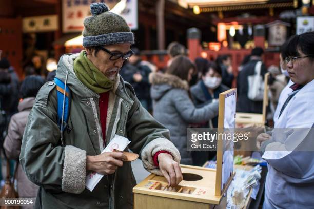 A visitor donates money to receive his 'omikuji' fortunetelling paper strips after praying for the new year at Tsurugaoka Hachimangu Shinto shrine on...