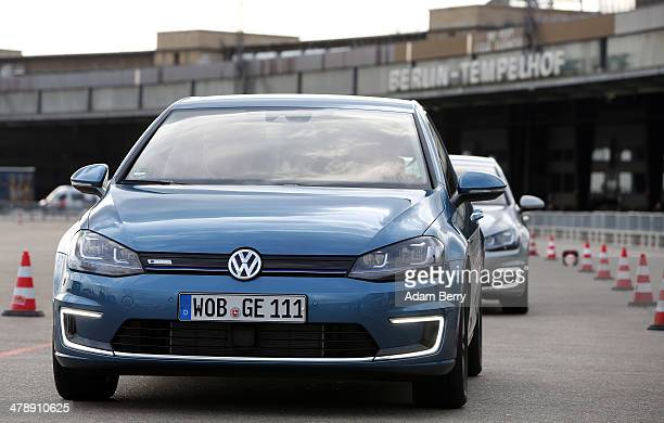 Visitor drives a Volkswagen e-Golf electric automobile at the Electric Mobility Week , a public Volkswagen event at the former Tempelhof airport, on...