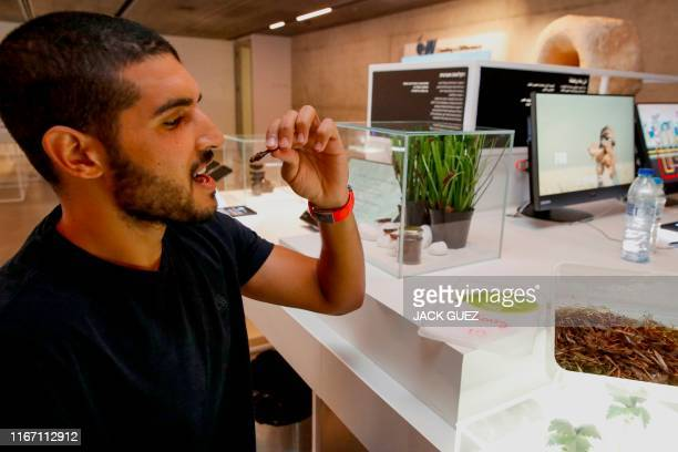 A visitor eats a grasshopper farmed as a Kosher proteinrich food source by Hargol FoodTech at the Israeli Expo technology exhibit at the Peres Center...