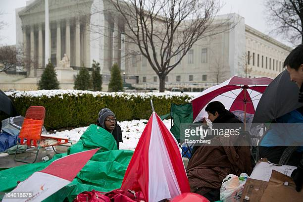 Visitor Ebony Miller left talks to fellow high school students while sitting underneath a tarp in line outside the Supreme Court building in...