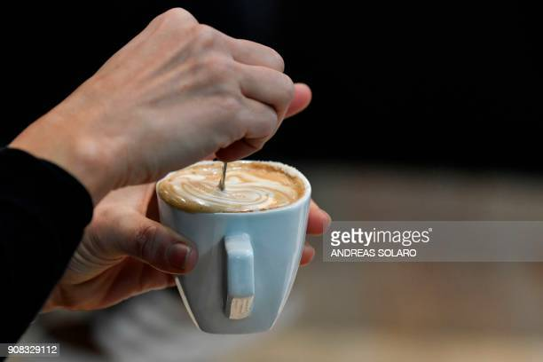 A visitor enjoys a cappuccino during the 39th International trade Show of Artisan Gelato Pastry Bakery and Coffe World in Rimini on January 21 2018 /...