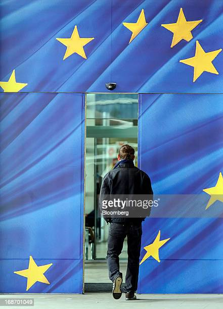 A visitor enters a doorway illustrated with the European Union flag and into the headquarters of the European Union Commission building in Brussels...