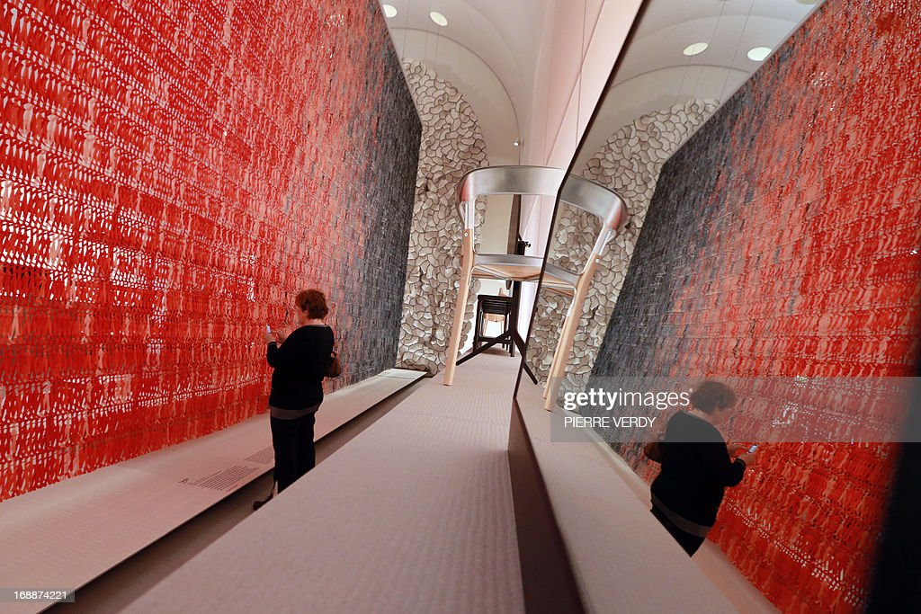 A visitor examines a piece at an exhibition covering the work of design team Ronan & Erwan Bouroullec, formed by the two brothers from Brittany, at the Musee des Arts Decoratifs in Paris on May 16, 2013.