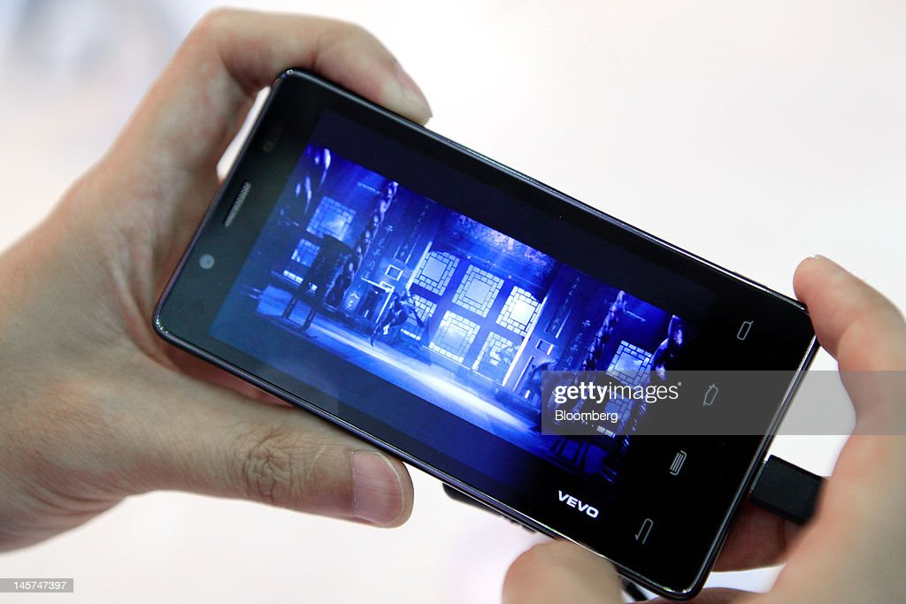 A visitor examines an Intel Corp. smartphone at the company's booth at Computex Taipei 2012 in Taipei, Taiwan, on Tuesday, June 5, 2012. Computex Taipei 2012 takes place from June 5 to June 9. Photographer: Ashley Pon/Bloomberg via Getty Images