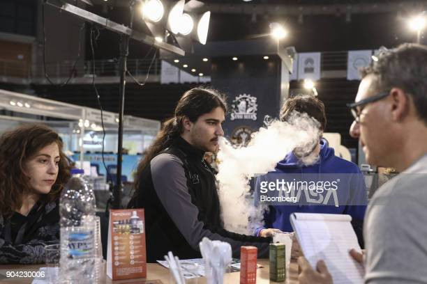 A visitor exhales vapor while testing an electronic ecigarette device at the 1st International Cannabis Expo at the Faliro Sports Pavilion in Athens...
