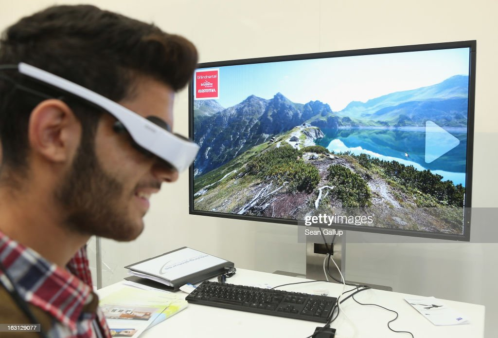 A visitor explores a digital mountain landscape with a Cinimeizer pair of digital goggles that track the movements of the wearer's head at the Zeiss stand at the 2013 CeBIT technology trade fair on March 5, 2013 in Hanover, Germany. CeBIT will be open March 5-9.