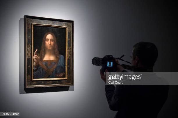 A visitor films a painting by Leonardo da Vinci entitled 'Salvator Mundi' before it is auctioned in New York on November 15 at Christies on October...