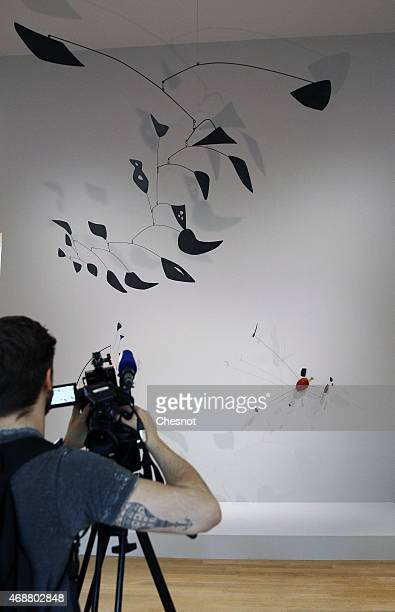 A visitor films an artwork by US artist Alexander Calder during the press opening of the exhibition 'Icones Americaines' at the Grand Palais on April...