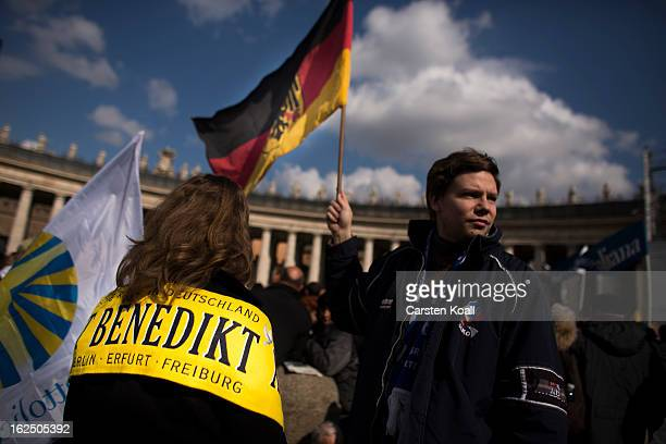 A visitor from germany wears a banner reading Benedict beside a man holding a german flag on February 24 2013 in Vatican City Vatican Pope Benedict...