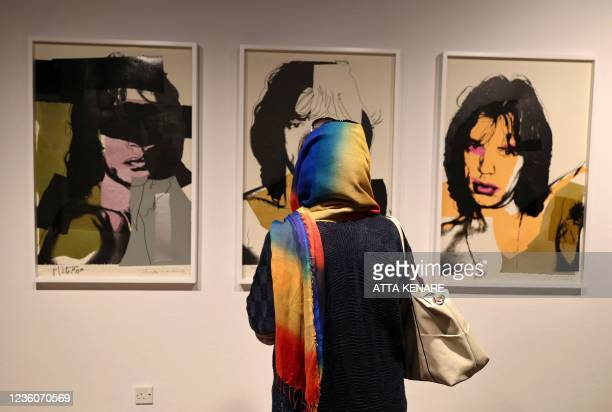 Visitor gazes at late US pop artist Andy Worhol's 1975 prints of Mick Jagger, the lead singer in British rock and roll band The Rolling Stones,...