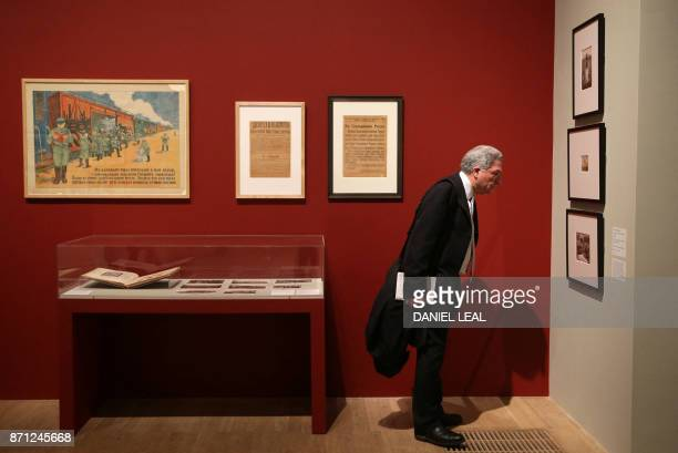 A visitor gazes at photographs on display during the 'Red Star over Russia A revolution in Visual Culture 190555' exhibition at the Tate Modern in...