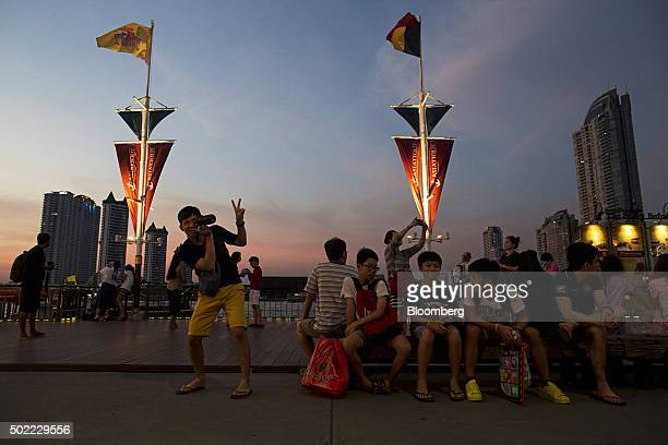 A visitor gestures as he takes a photograph at Asiatique The Riverfront openair mall in Bangkok Thailand on Friday Dec 18 2015 Thai economic...