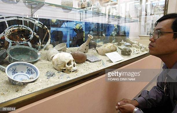 Visitor gets a close look at utensils from an ancient boat's crew on display at an exhibition of ancient porcelain and ceramics recovered from sunk...