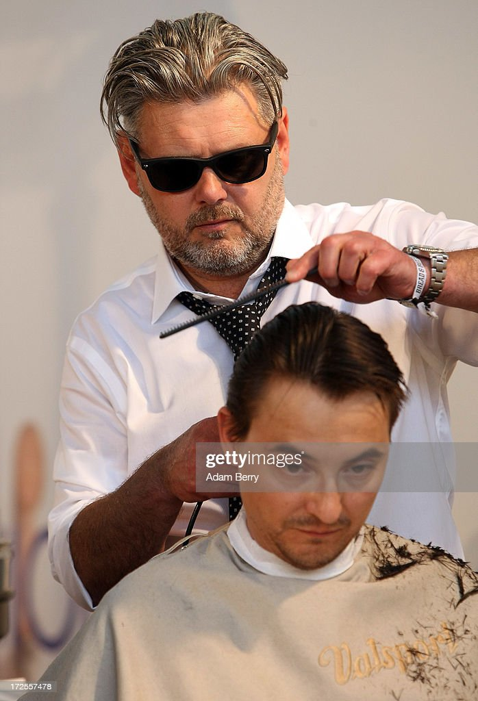 A visitor gets a free haircut at the Bread and Butter trade show at the former Tempelhof airport during Mercedes-Benz Fashion Week in Berlin on July 3, 2013 in Berlin, Germany.