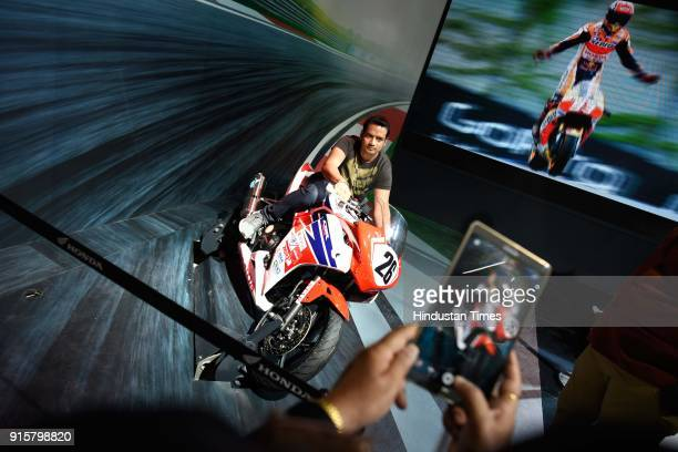 A visitor gets himself photographed with Honda sports CBR during Auto Expo Motor Show 2018 on February 8 in Greater Noida India