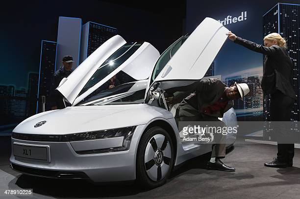 Visitor gets out of a Volkswagen XL1 plug-in diesel-electric hybrid automobile on display at the Electric Mobility Week , a public Volkswagen event...