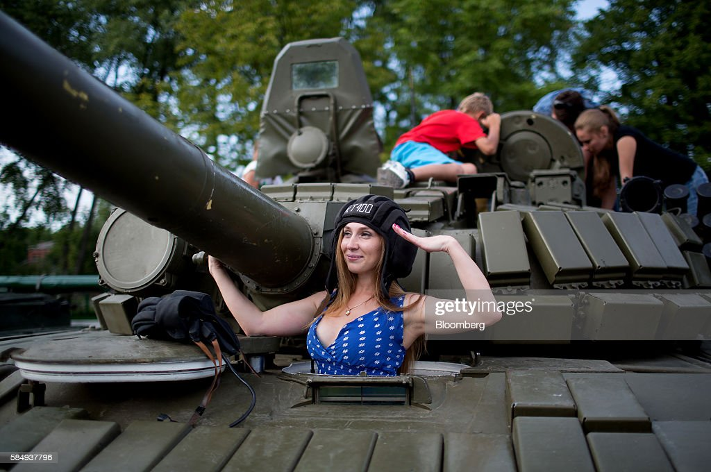 A visitor gives a military salute while posing for a photograph in the hatch of a T-72 Soviet era battle tank at a display of military hardware during Russian Navy day at the Vistula lagoon in Baltiysk, Russia, on Sunday, July 31, 2016. Amid Russia's recent rearmament, the Kaliningrad region has increasingly returned to its Soviet-era role as a garrison on the strategic Baltic Sea coast. Photographer: Andrey Rudakov/Bloomberg via Getty Images