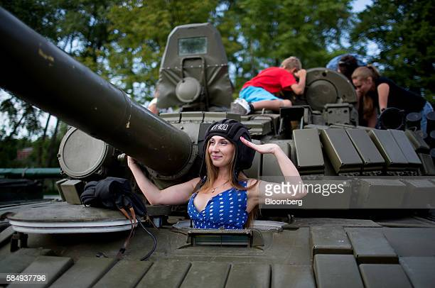 A visitor gives a military salute while posing for a photograph in the hatch of a T72 Soviet era battle tank at a display of military hardware during...
