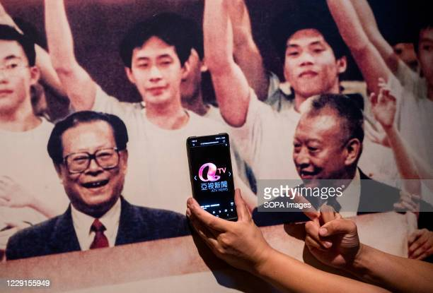 """Visitor gives the middle finger in front of a portrait of former Chinese leader Jiang Zemin at the exhibition """"The Hong Kong Story"""" at the Hong Kong..."""