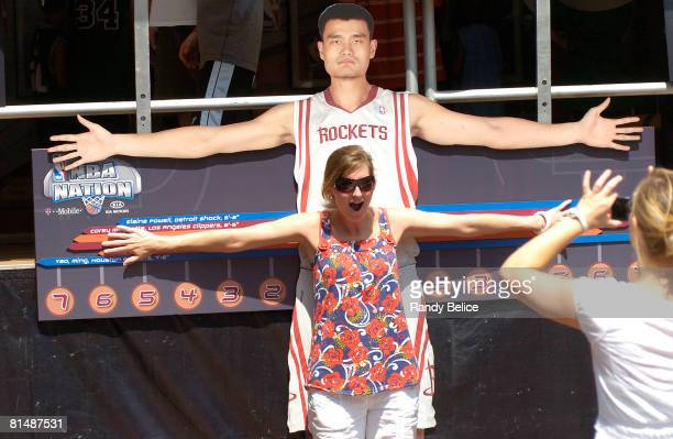 A visitor has her arm span photographed against the likeness of Yao Ming as part of the NBA Nation Tour stop at Boston City Hall Plaza in conjunction...