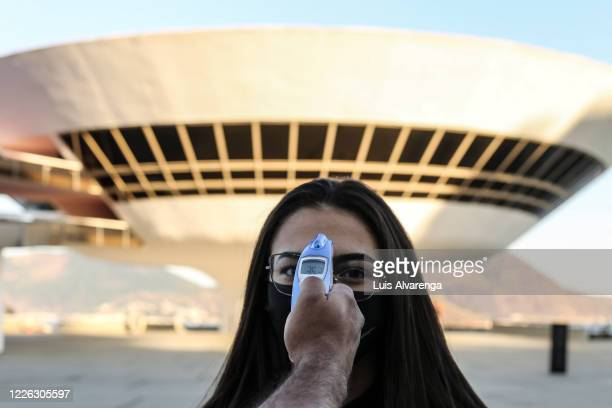 Visitor has their temperature measured at the entrance to the Museum of Contemporary Art amidst the coronavirus pandemic on July 11, 2020 in Niteroi,...