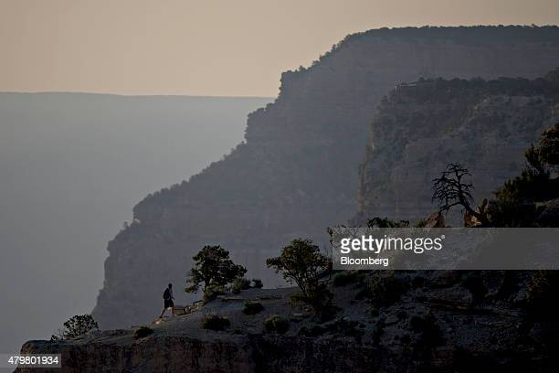 A visitor hikes along a ridge on the South Rim of Grand Canyon National Park in Grand Canyon Arizona US on Thursday June 25 2015 The Grand Canyon has...