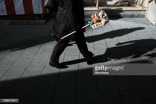 Visitor holding a Kumade bamboo rake decorated with good luck charms walks at the Kanda Myojin shrine in Tokyo, Japan, on Monday,Jan. 4, 2021....
