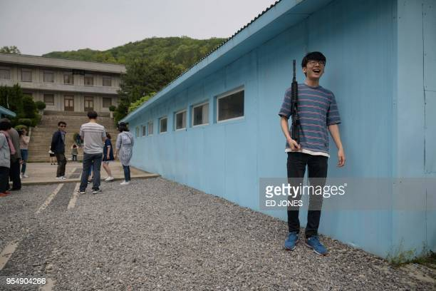 A visitor holding a mock rifle poses for photos at a replica of the DMZ border truce village of Panmunjom built as a film set near Namyangju east of...