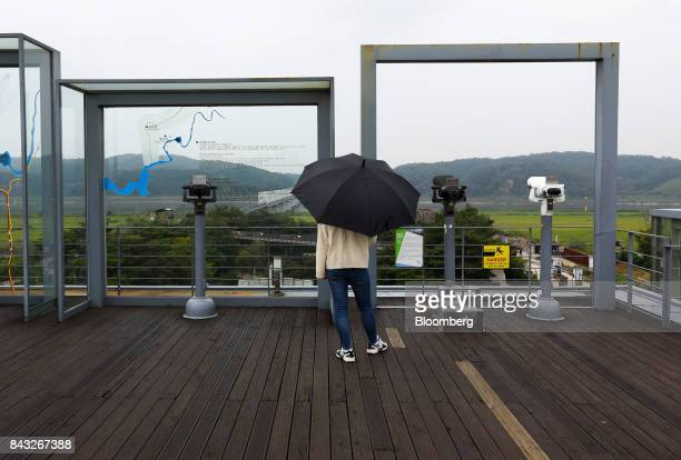 A visitor holding an umbrella looks across to the north side of the border at the Imjingak pavilion near the Demilitarized Zone in Paju South Korea...