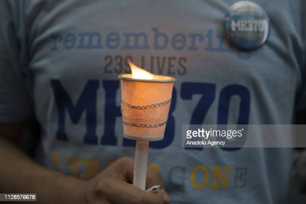 Visitor holds a lit candle to pay tribute to missing passengers during a commemoration event to mark the 5th anniversary of the missing Malaysia...