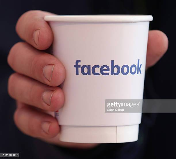 A visitor holds a paper coffee cup adorned with the Facebook logo at the Facebook Innovation Hub on February 24 2016 in Berlin Germany The Facebook...